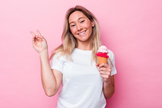 Junge australische frau, die ein eis hält, das auf rosafarbenem hintergrund freudig und sorglos isoliert ist und ein friedenssymbol mit den fingern zeigt.
