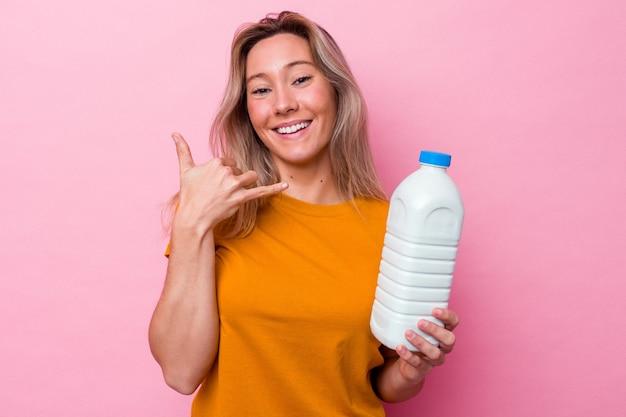 Junge australische frau, die eine flasche milch einzeln auf rosafarbenem hintergrund hält, die eine handyanrufgeste mit den fingern zeigt.