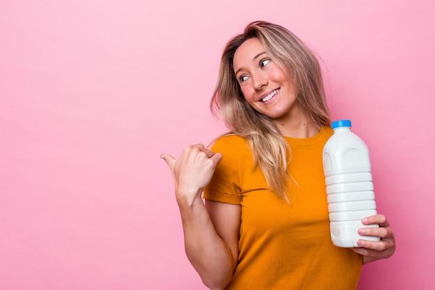 Junge australische frau, die eine flasche milch einzeln auf rosafarbenem hintergrund hält, zeigt mit dem daumen weg, lacht und sorglos