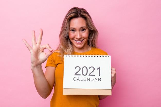 Junge australische frau, die einen kalender einzeln auf rosafarbenem hintergrund hält, fröhlich und selbstbewusst, der eine ok geste zeigt.