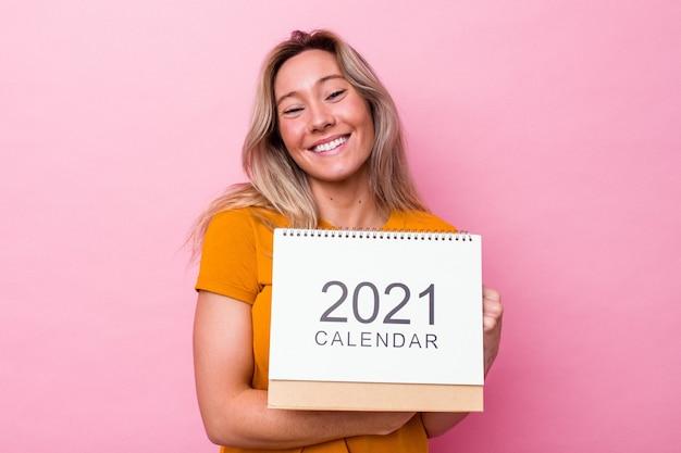 Junge australische frau, die einen kalender hält, der auf rosa hintergrund isoliert ist, lacht und spaß hat.