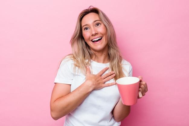 Junge australische frau, die einen rosa becher lokalisiert auf rosa hintergrund hält, lacht laut und hält hand auf brust.