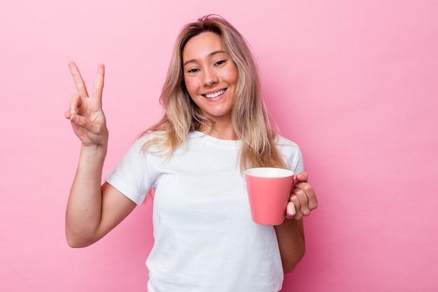 Junge australische frau, die einen rosafarbenen becher einzeln auf rosafarbenem hintergrund hält, freudig und sorglos, der ein friedenssymbol mit den fingern zeigt.