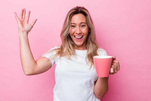Junge australische frau, die einen rosafarbenen becher einzeln auf rosafarbenem hintergrund hält und eine angenehme überraschung empfängt, aufgeregt und die hände hebt.