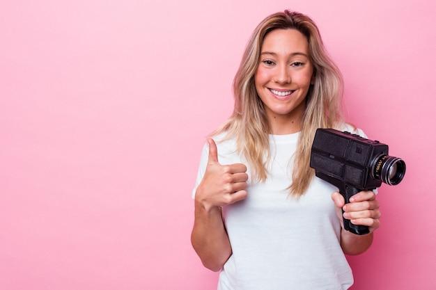 Junge australische frau, die mit einer vintage-videokamera filmt, lächelt isoliert und hebt den daumen hoch