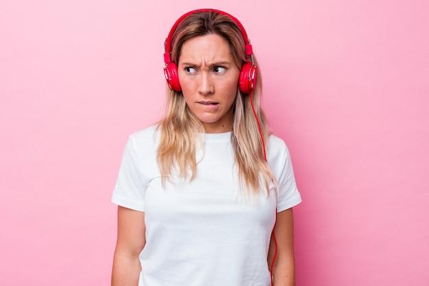 Junge australische frau, die musik einzeln auf rosafarbenem hintergrund hört, verwirrt, fühlt sich zweifelhaft und unsicher.