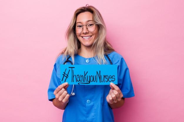 Junge australische krankenschwesterfrau, die ein internationales krankenschwestern-tagesplakat lokalisiert auf blauem hintergrund hält