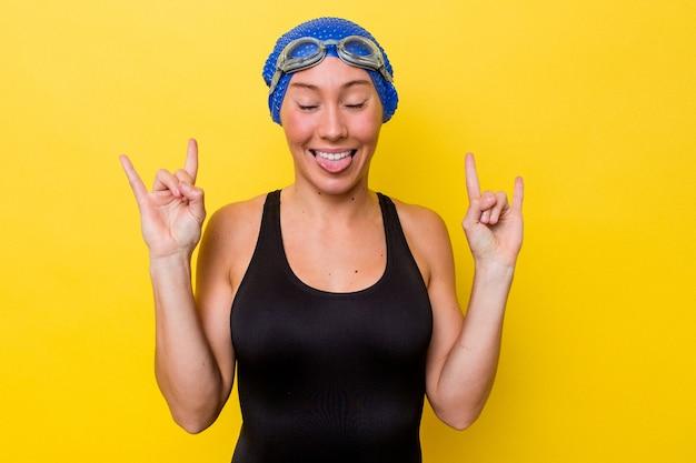 Junge australische schwimmerfrau lokalisiert auf gelbem hintergrund, der felsengeste mit den fingern zeigt