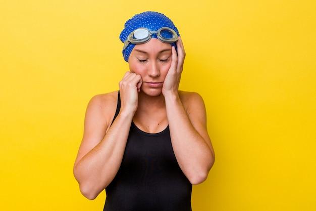 Junge australische schwimmerfrau lokalisiert auf gelbem hintergrund, der trostlos jammert und weint.