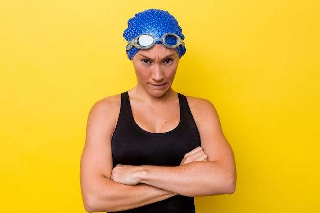 Junge australische schwimmerin, die auf gelbem hintergrund isoliert ist, runzelt das gesicht vor unmut, hält die arme verschränkt.