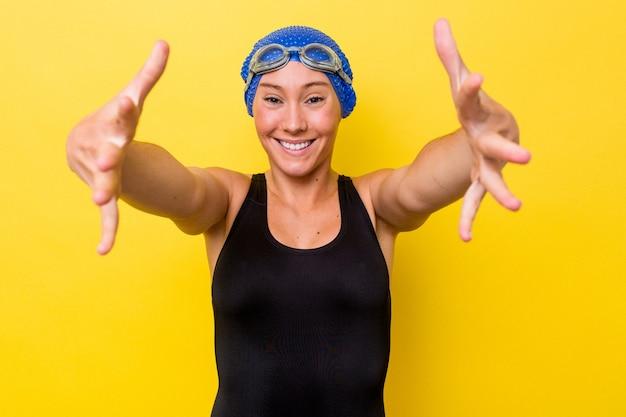Junge australische schwimmerin, die auf gelbem hintergrund isoliert wird, fühlt sich zuversichtlich, eine umarmung zur kamera zu geben.