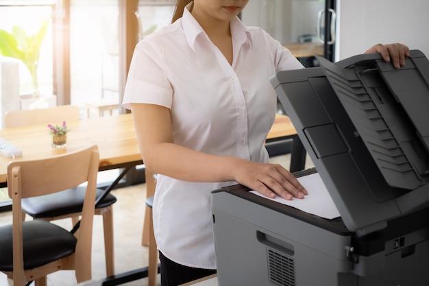 Junge auszubildendefrau im einheitlichen gebrauchdrucker, um wichtige und vertrauliche dokumente im büro zu scannen