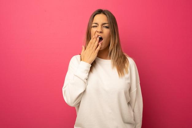 Junge authentische charismatische echte menschenfrau gegen eine wand, die gähnt und eine müde geste zeigt, die mund mit hand bedeckt.