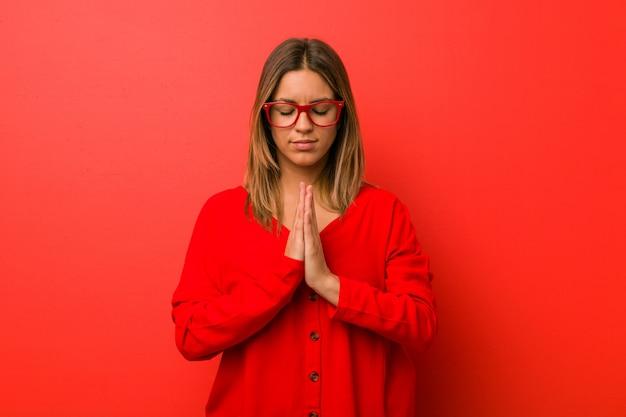 Junge authentische charismatische wirkliche leutefrau gegen ein wandhändchenhalten beten herein nahe mund, glaubt überzeugt.