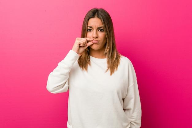Junge authentische charismatische wirkliche leutefrau gegen eine wand mit den fingern auf den lippen, die ein geheimnis halten.