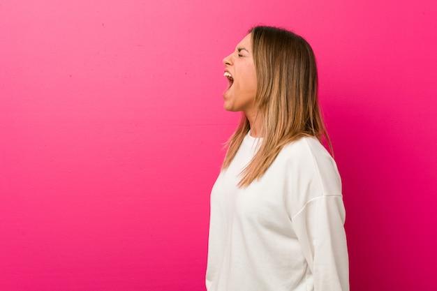 Junge authentische charismatische wirkliche leutefrau gegen eine wand schreiend in richtung zu einem kopienraum