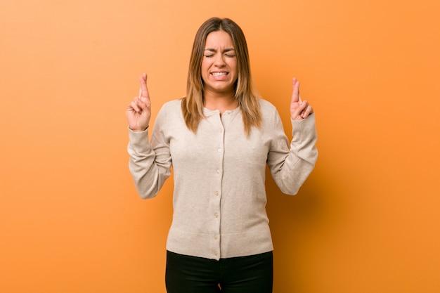 Junge authentische charismatische wirkliche leutefrau gegen finger einer wandüberfahrt für das haben des glücks