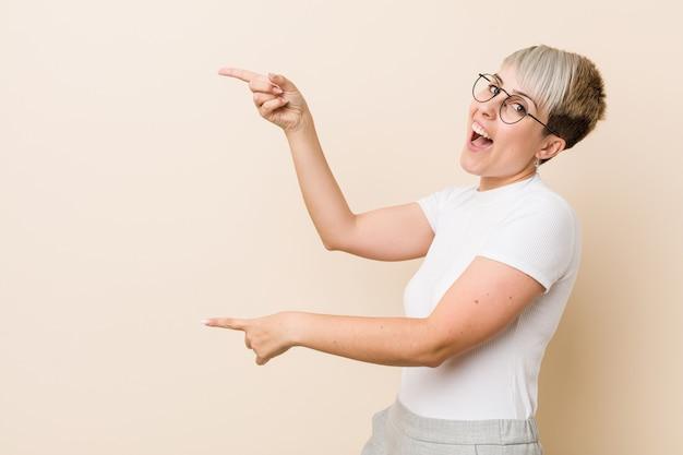 Junge authentische natürliche frau, die ein aufgeregtes weißes hemd trägt, das mit zeigefingern weg zeigt.