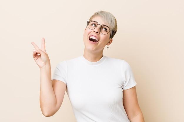 Junge authentische natürliche frau, die ein weißes hemd froh und sorglos zeigt ein friedenssymbol mit den fingern trägt.