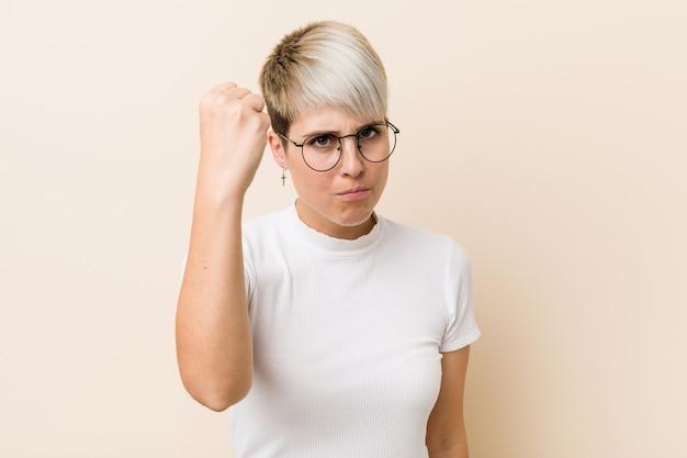 Junge authentische natürliche frau, die ein weißes hemd zeigt faust zur kamera, aggressiver gesichtsausdruck trägt.