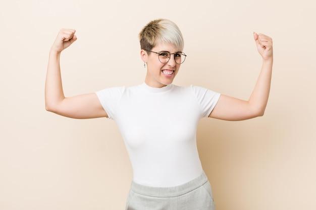 Junge authentische natürliche frau, die ein weißes hemd zeigt stärkegeste mit den armen, symbol der weiblichen energie trägt