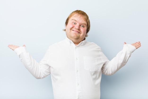 Junge authentische rothaarige dicker mann macht die waage mit den armen, fühlt sich glücklich und zuversichtlich.
