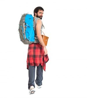 Junge backpacker zu fuß über weißem hintergrund