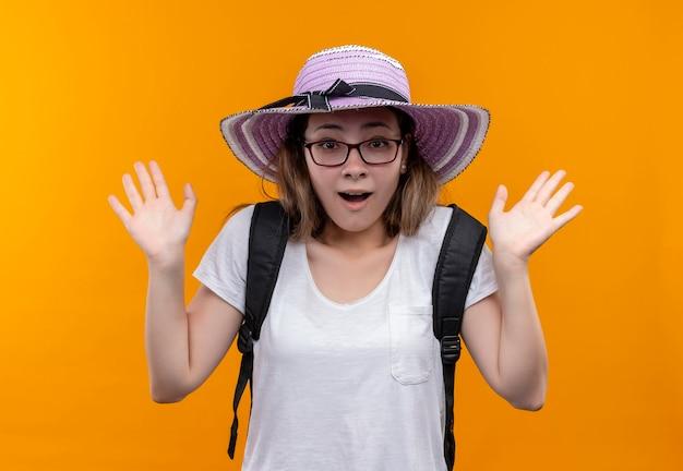 Junge backpackerfrau im weißen t-shirt, das sommerhut mit dem rucksack lächelnd fröhlich schauend überrascht steht über orange wand trägt