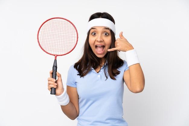 Junge badmintonspielerfrau über der lokalisierten weißen wand, die telefongeste macht. rufen sie mich zurück zeichen
