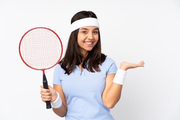 Junge badmintonspielerin auf isoliertem weiß, das imaginären copyspace auf der handfläche hält, um eine anzeige einzufügen
