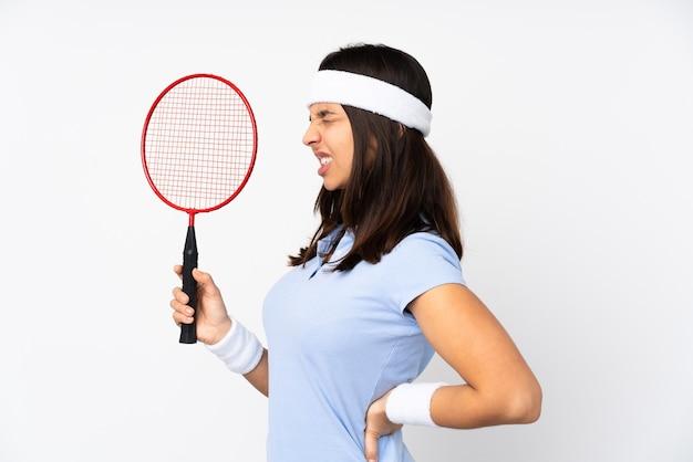 Junge badmintonspielerin auf isoliertem weiß, das unter rückenschmerzen leidet, weil sie sich bemüht hat
