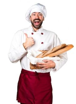 Junge bäcker hält etwas brot und mit daumen nach oben