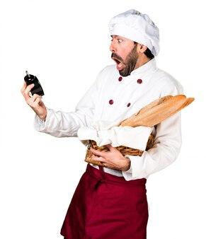 Junge bäcker halten einige brot und halten vintage uhr