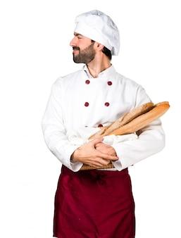 Junge bäcker halten etwas brot und suchen seitlich