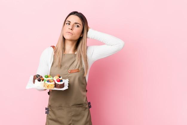 Junge bäckerfrau, welche die bonbons berühren zurück vom kopf hält, eine wahl denkt und trifft