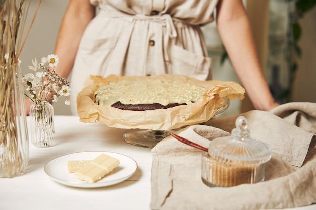 Junge bäckerin, die einen köstlichen schokoladenkuchen mit sahne auf einem weißen tisch macht