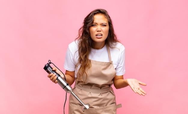 Junge bäckerin sieht wütend, genervt und frustriert schreiend wtf aus oder was ist los mit dir