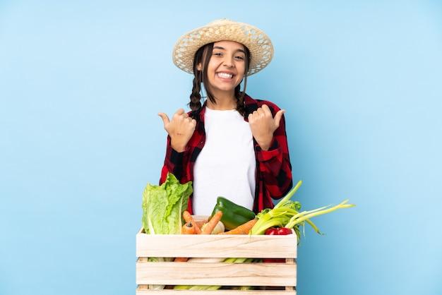 Junge bäuerin, die frisches gemüse in einem holzkorb mit daumen hoch geste hält und lächelt