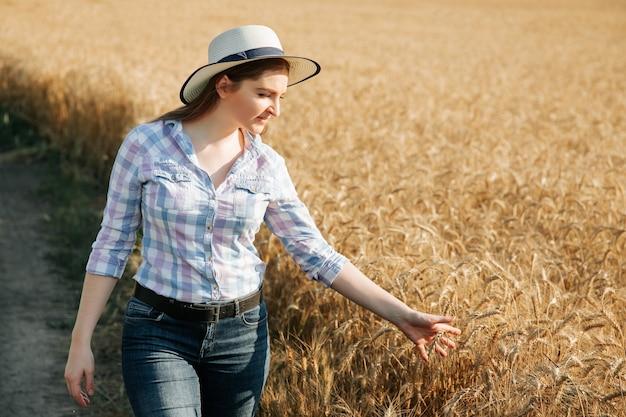 Junge bäuerin im weizenfeld untersucht ernte bei sonnenuntergang junge bäuerin mit hut und hemd in...