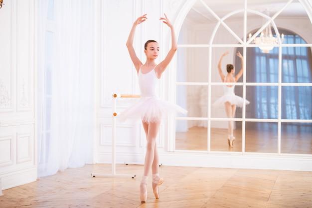 Junge ballerina, die auf spitze in einem tutu in einer schönen weißen halle vor dem spiegel steht.