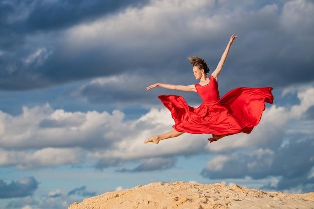 Junge ballerina in einem roten langen kleid tanzen