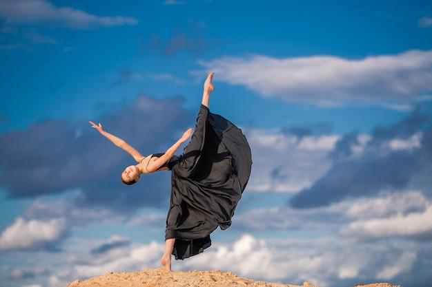 Junge ballerina in einem schwarzen langen kleid tanzen
