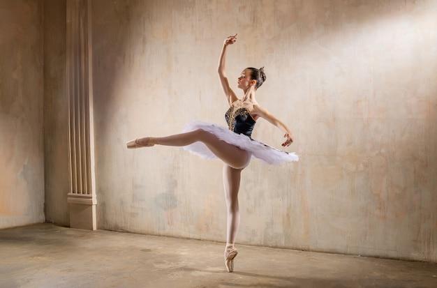 Junge ballerina in einem weißen tutu, das im scheinwerferlicht in einer weinlese-szene tanzt