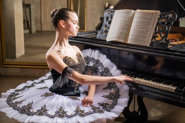 Junge ballerina in einem weißen tutu spielt ein schönes altes klavier