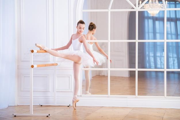 Junge ballerina macht klassisches ballett in einer ballettscheune in einem schönen weißen raum vor einem spiegel.