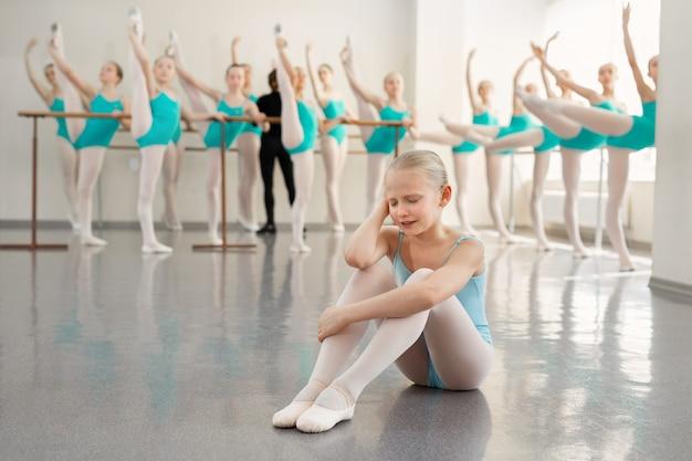 Junge ballerina weint in der tanzhalle. tränen einer kleinen ballerina in einer ballettschule