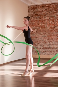 Junge ballerina-wiederholung. rhythmische gymnastik. jugendsport, gesunder jugendlicher lebensstil. selbstbewusstes mädchen mit grünem band, tanzkurshintergrund, übungskonzept