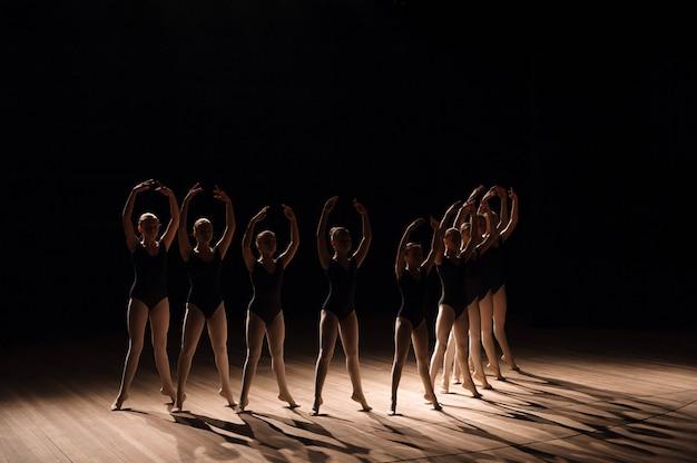 Junge ballerinas, die einen choreografierten tanz üben, regnen während des übens in einer ballettschule alle ihre arme in anmutiger übereinstimmung