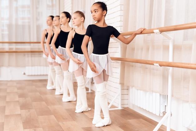 Junge ballerinas, die in der ballettklasse proben.