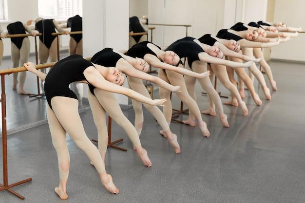 Junge ballerinas machen übungen im studio. junge ballettschauspielerinnen, die tanzbewegung an der ballettbarre in der tanzklasse trainieren. flexibilität und fähigkeiten junger ballerinakörper